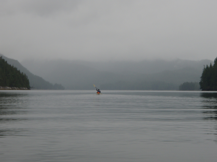 A kayaker paddles across the water as mist engulfs the mountains in the background.
